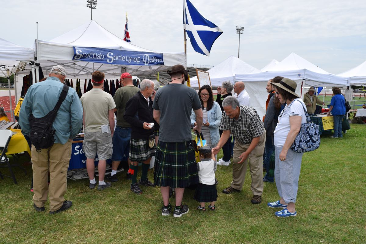J. Aitken (4th from left) works the Society's tent at the 2016 Arlington games.